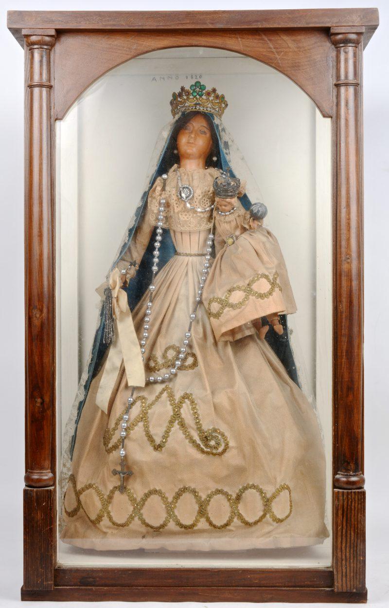 Een wassen madonna en kind met volledige originele kleding, versierd met kant. In oorspronkelijke vitrine. XIXde eeuw.