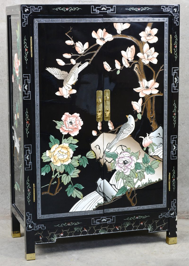 Een zwartgelakt Chinees tweedeurskastje met meerkleurig decor van bloemen en vogels.