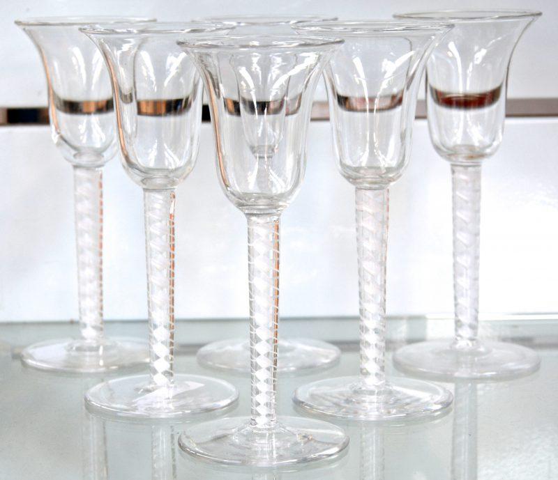 Een reeks van zes antieke glazen borrelglaasjes. De stam versierd met spiraalvormige inclusies.