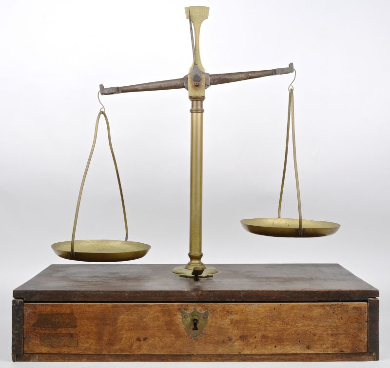 Een antieke weegschaal van hout en koper met een lade, voorzien van gewichtjes.