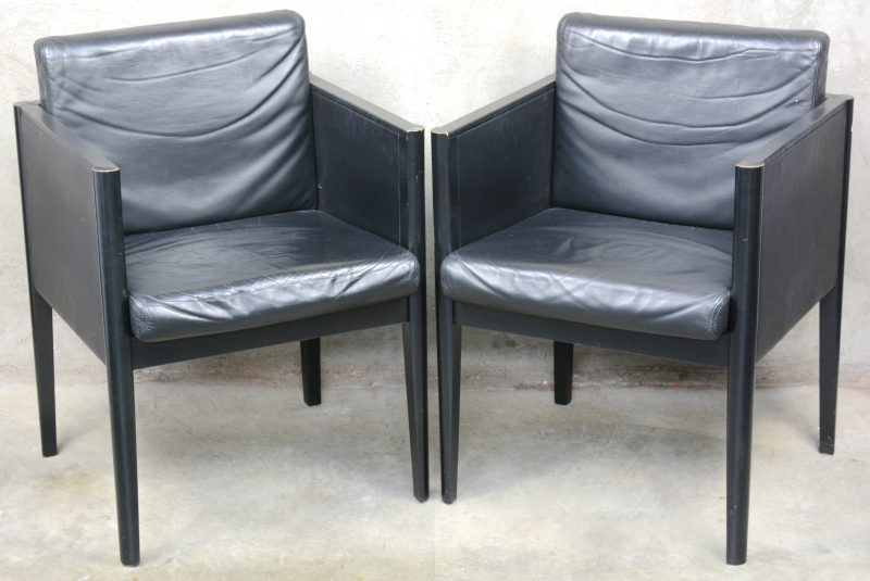 Een paar vierkante fauteuils met zwart lederen bekleding.