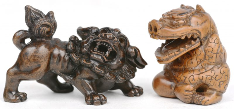 Een paar fijn gesculpteerde netsuké's, waarbij één in de vorm van een Fo-hond en de andere in de vorm van een man met een drakenmasker. Beide gesigneerd.
