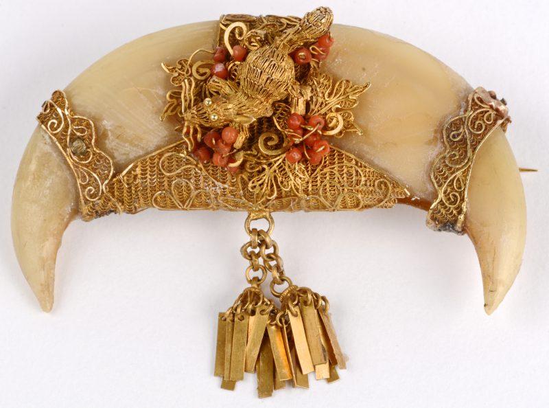 Een broche van een dubbele Birmaanse tijgerklauw, bezet met 14 karaats gouden filigraanwerk in de vorm van een muisje, versierd met koraal.