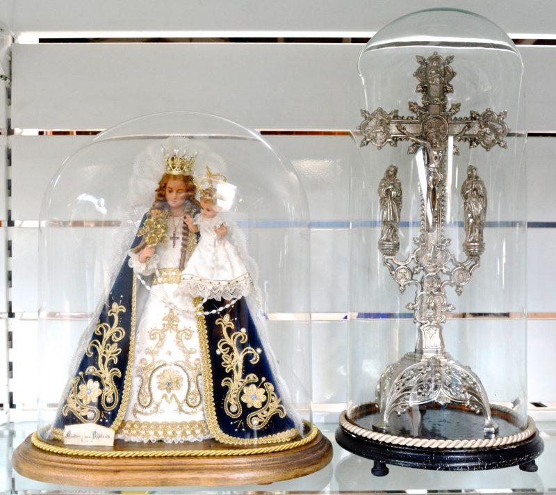 Een wassen Madonna met kind en een verzilverd kruisbeeld. Beide onder stolp.