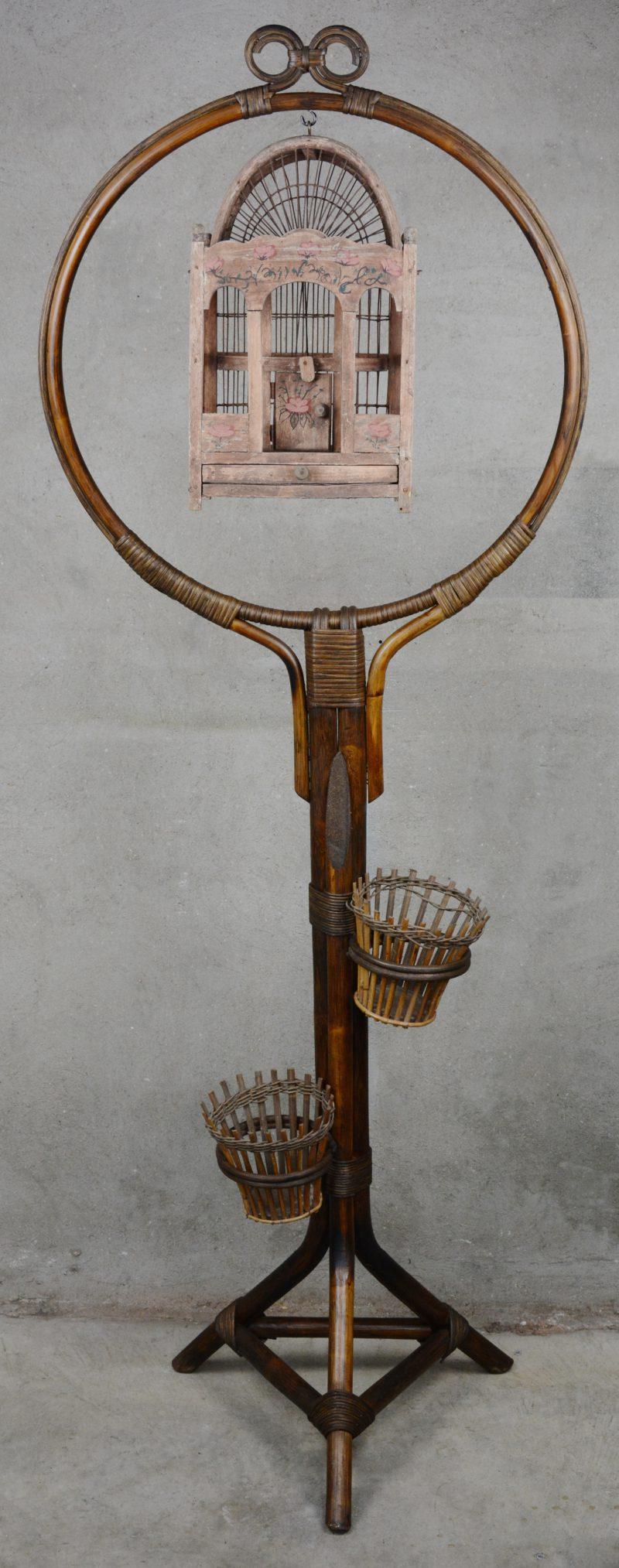 Een rotan staander met een houten vogelkooi.