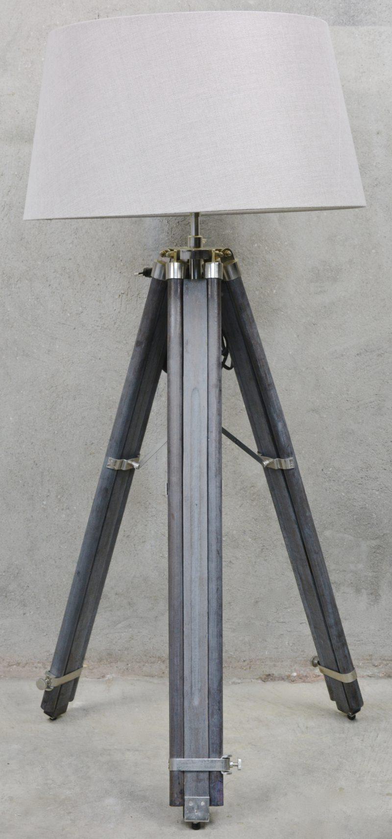Een staande lamp, de voet opgebouwd uit een grijsgepatineerd uitschuifbaar statief.