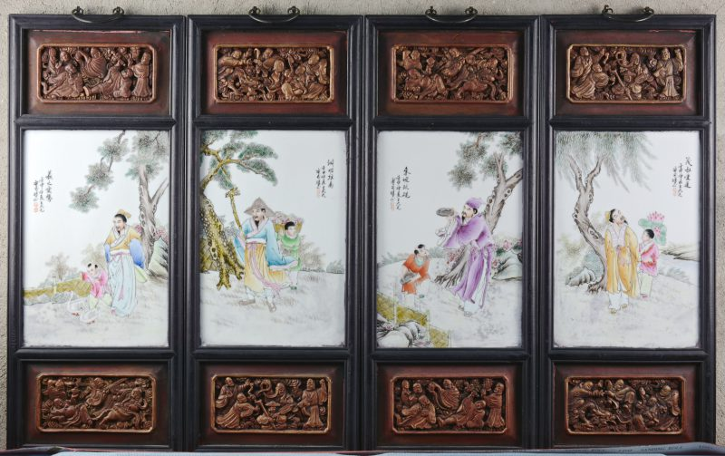Een reeks van vier porseleinen plaquettes met meerkleurige decors van personages in landschappen. In gesculpteerde houten lijsten. Chinees werk.