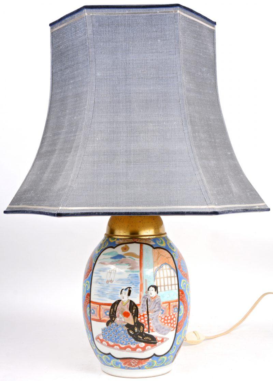 Een lampenvoet van Imariporselein met een meerkleurig decor van personages.