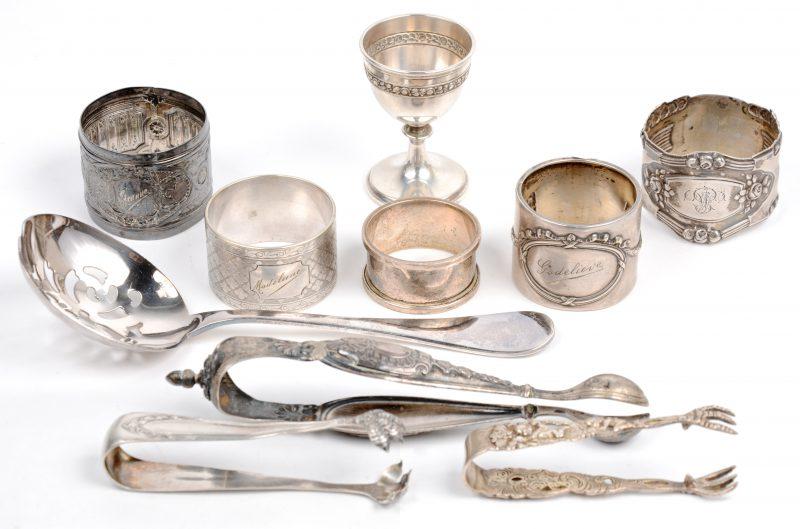 Een lot zilver, bestaande uit vier servetringen en drie suikertangen. Bijgevoegd een lepel en een servetring van Christofle.