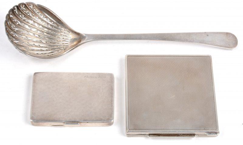 Een zilveren strooilepel en poederdoosje, respectievelijk 935 & 835 promille. Evenals een zilveren doosje met Duitse keuren en met inscriptie Ostern 1938.