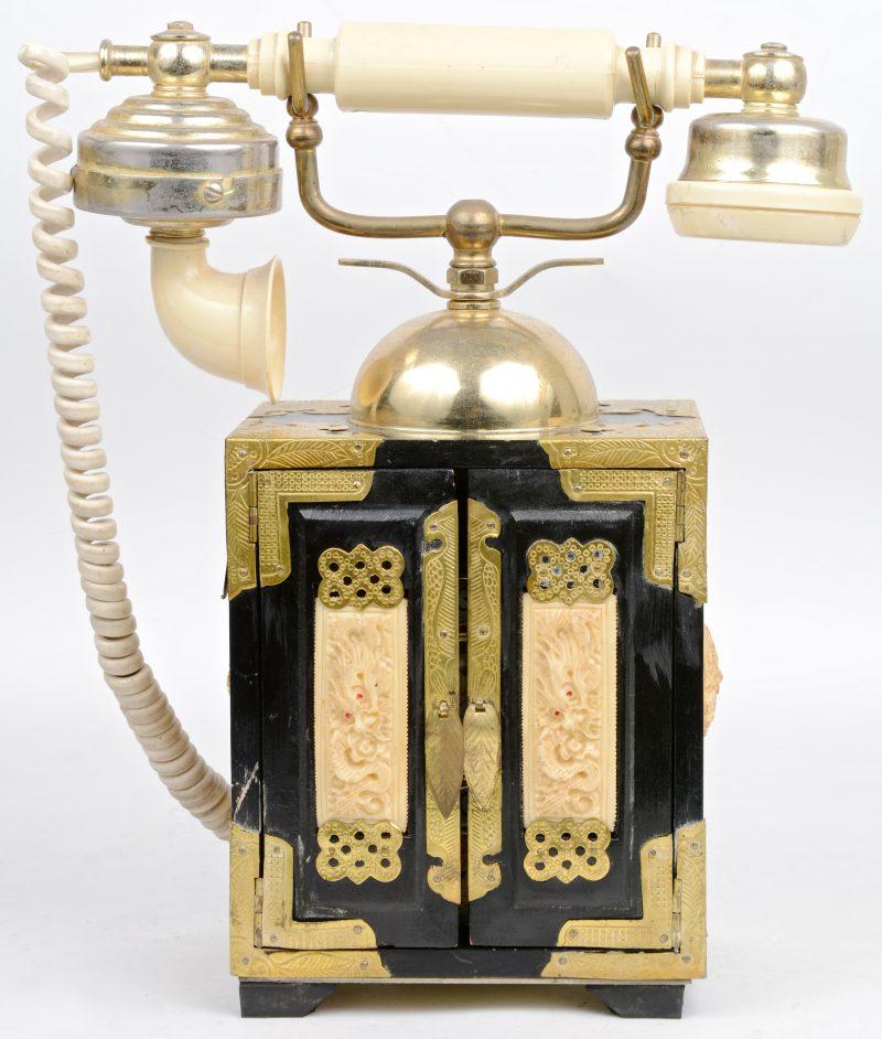 Een oude Chinese telefoon met draaischijf in het met messing beslagen houten kastje.