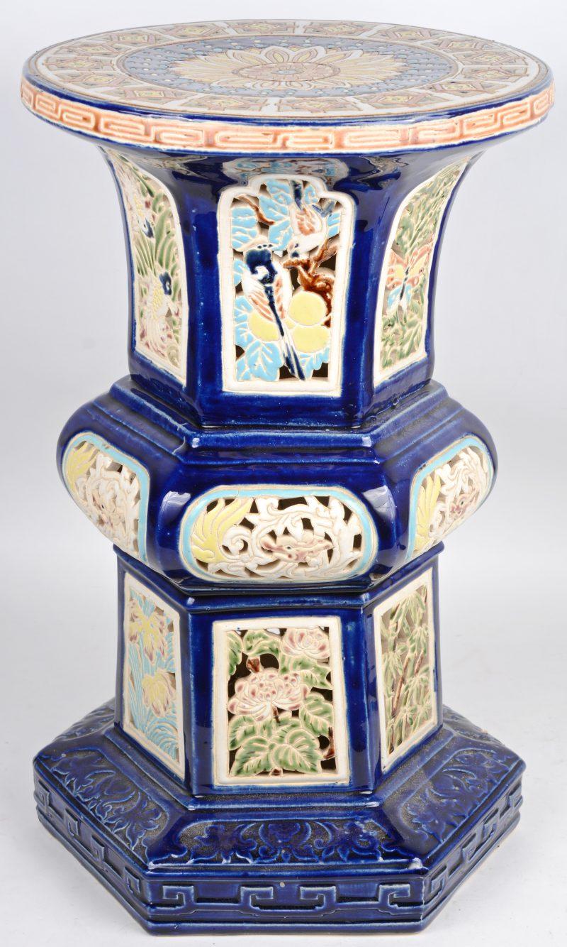Een piedestal van opengewerkt aardewerk, versierd met een meerkleurig decor van dieren en bloemen op blauwe fond.