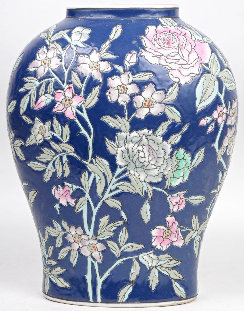 Een platte balustervaas van Chinees porselein met een meerkleurig bloemendeocr in reliëf op blauwe fond.