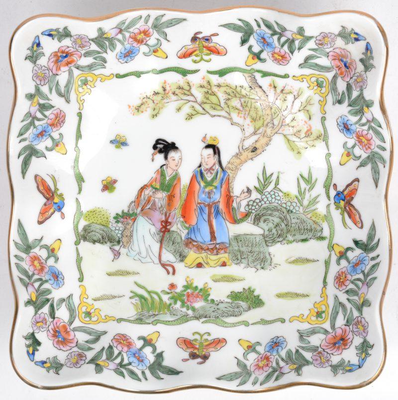 Een vierkant schaaltje van meerkleurig Chinees porselein met een decor van personages in een tuin en met vergulde rand. Onderaan gemerkt.