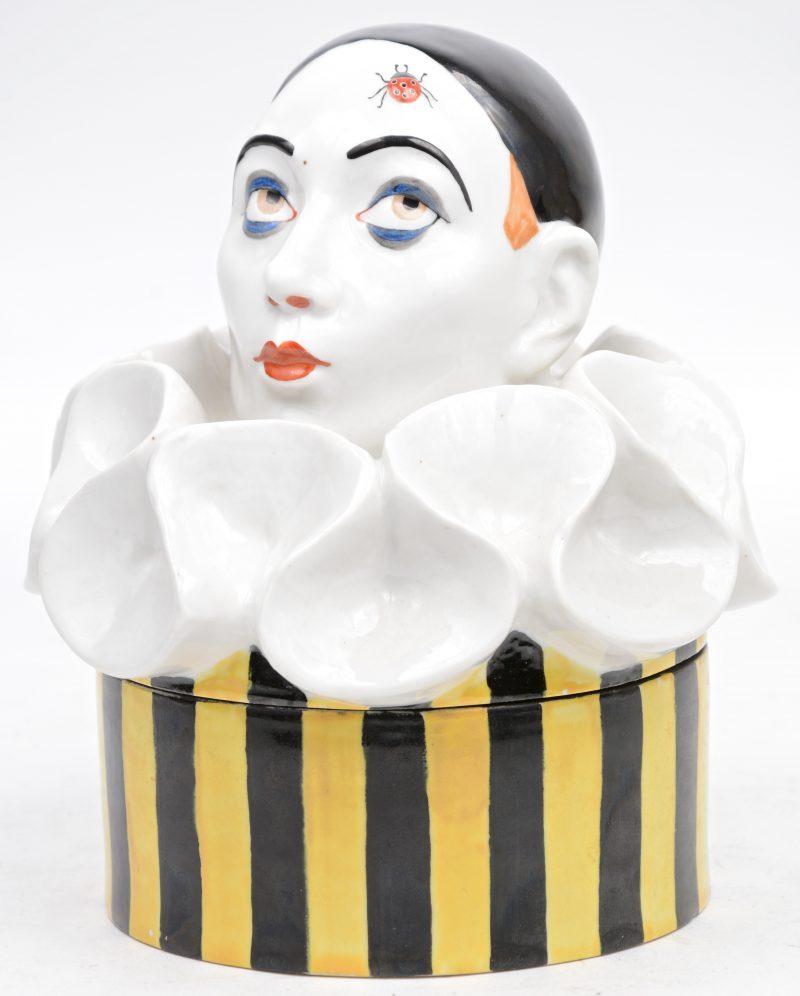 Een dekseldoos van meerkleurig porselein in de vorm van een pierrot met lieveheersbeestje. Naar ontwerp van Geneviève Granger. Onderaan gemerkt.