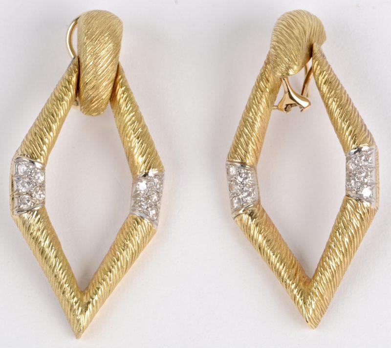 Een paar 18 karaats geel gouden oorbellen bezet met briljanten met een gezamenlijk gewicht van ± 1 ct.