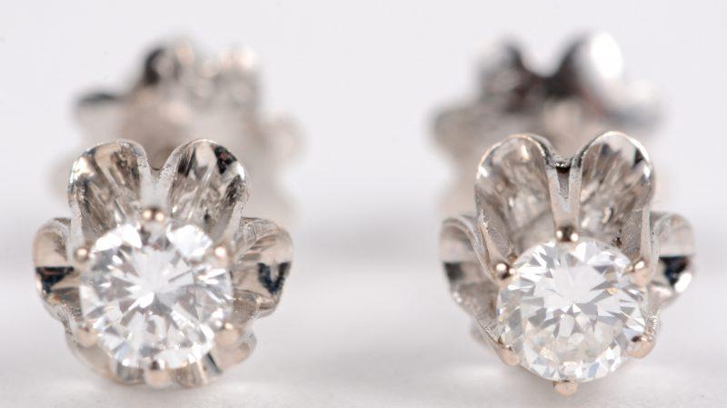 Een paar 18 karaats wit gouden oorbellen bezet met twee briljanten met een gezamenlijk gewicht van ± 0,20 ct.