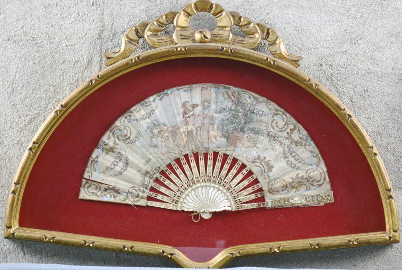 Een antieke waaier van ivoor en papier, versierd met een romantisch tafereel in gouache. Ingelijst.