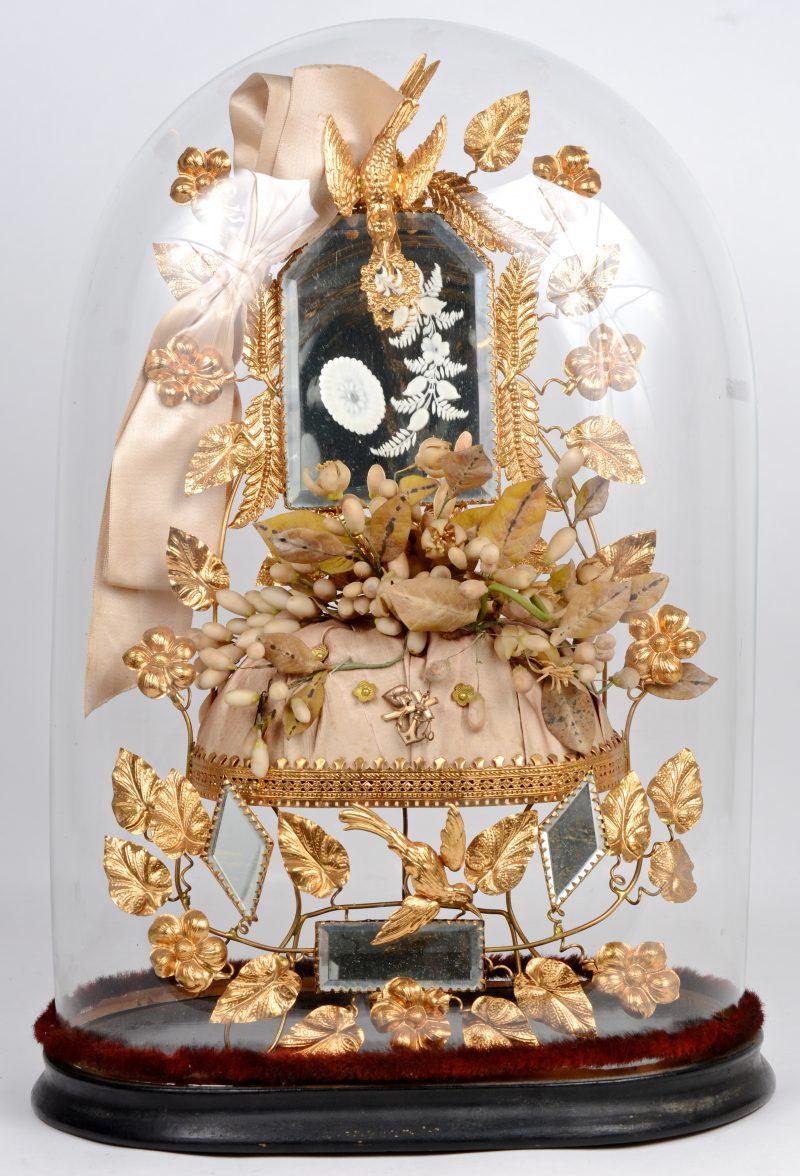 Een mondgeblazen bruidsstolp met gecapitonneerd kussentje en vergulde bladeren en bloemen en een vogeltje.