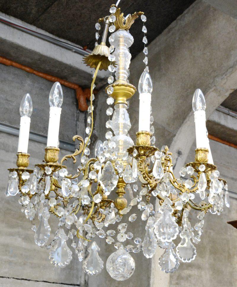 Een koperen luchter met acht lichtarmen en versierd met kristallen pendeloques.