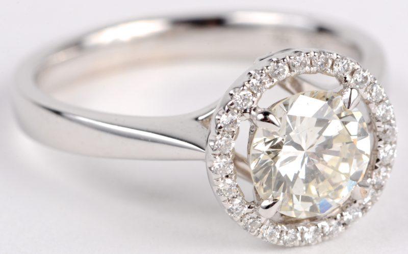 Een 18 karaats wit gouden ring bezet met een centrale diamant van ± 1,17 ct. J. SI1 en diamanten met een gezamenlijk gewicht ± 0,44 ct.