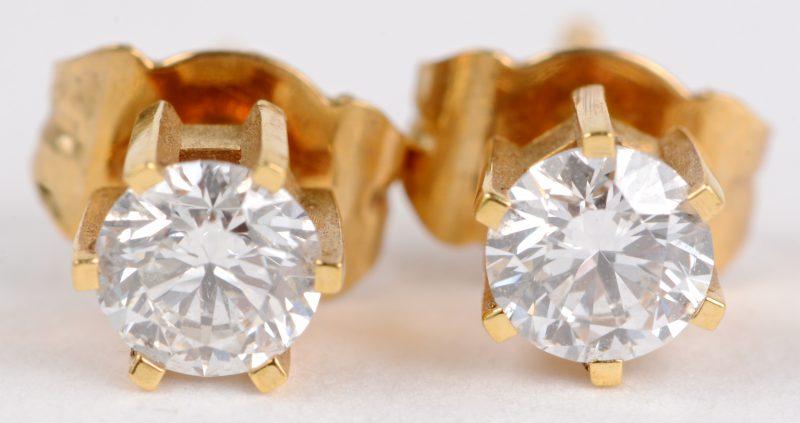 Een paar 18 karaats geel gouden oorbellen bezet met diamanten met een gezamenlijk gewicht ± 0,60 ct.