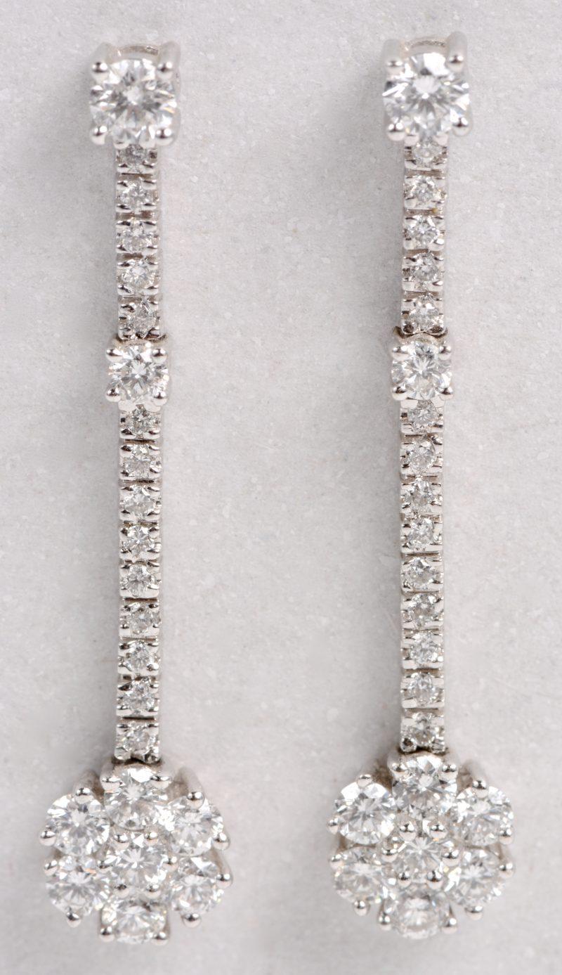 Een paar 18 karaats wit gouden oorbellen bezet met diamanten met een gezamenlijk gewicht ± 1,16 ct.