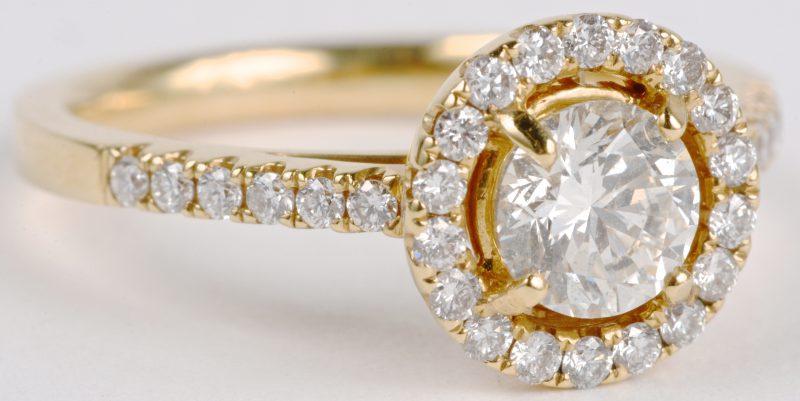 Een 18 karaats geel gouden ring bezet met een centrale diamant van ± 0,73 ct. en diamanten met een gezamenlijk gewicht ± 0,36 ct.
