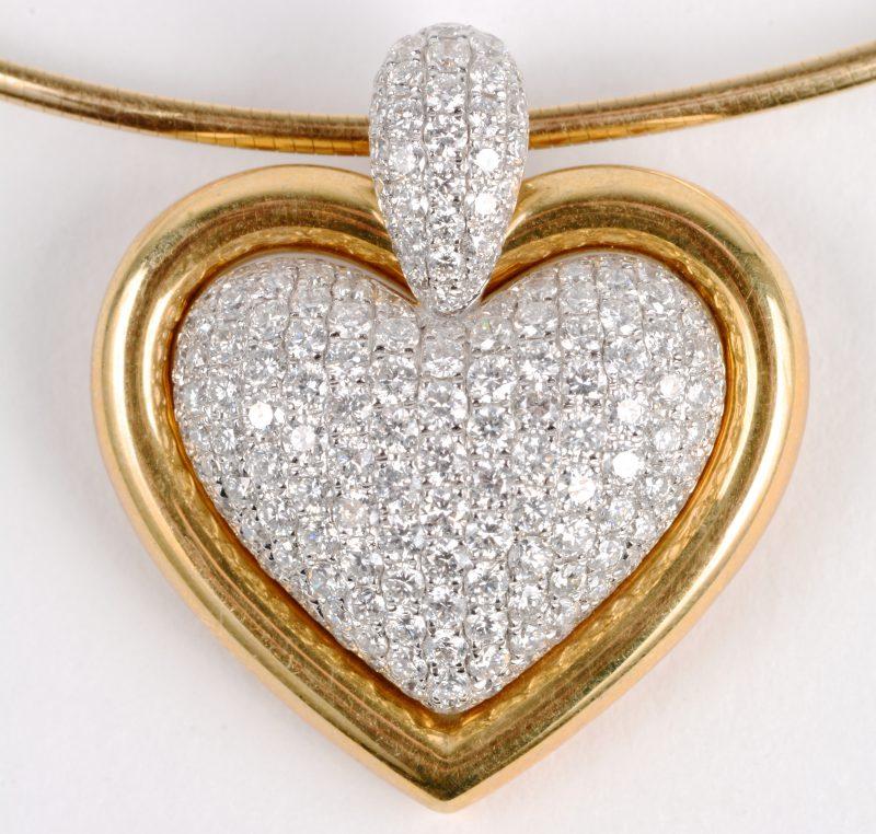 Een 18 karaats wit en geel gouden ketting met hanger in de vorm van een hart bezet met diamanten met een gezamenlijk gewicht ± 1,88 ct.