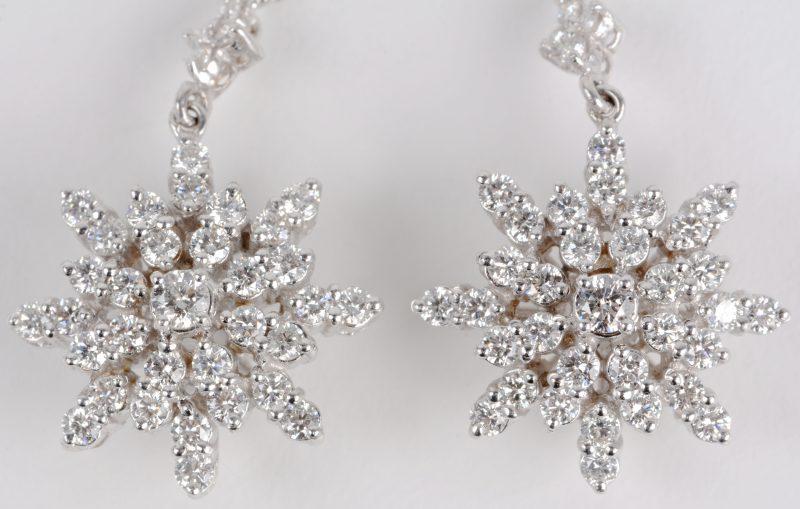 Een paar 18 karaats wit gouden bloemvormige oorbellen bezet met diamanten met een gezamenlijk gewicht ± 2,88 ct.