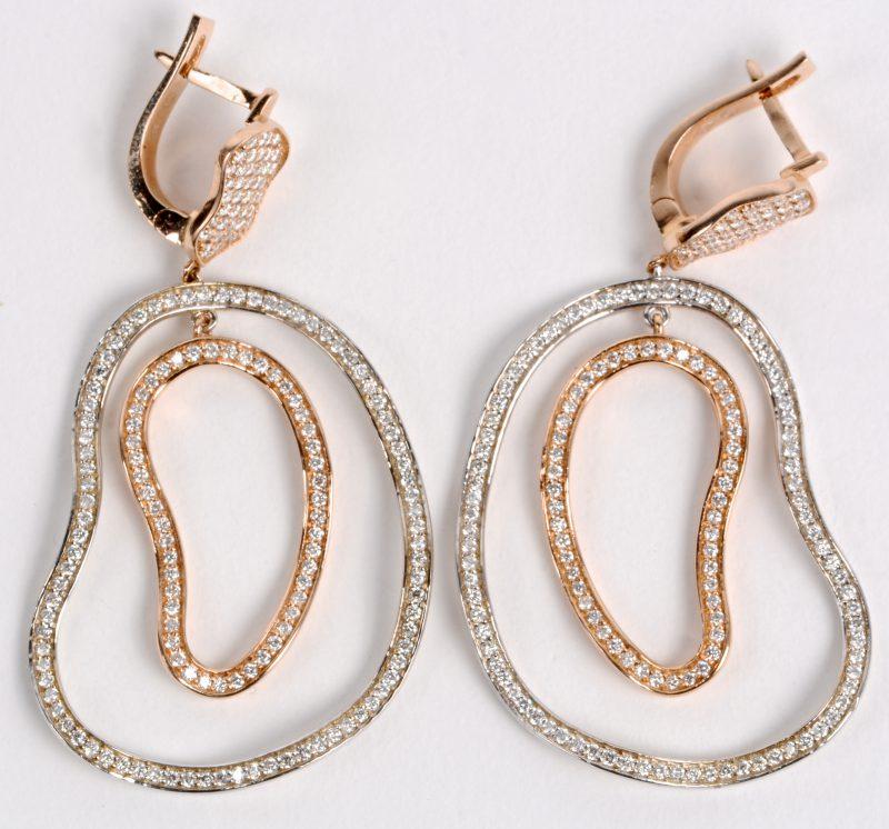 Een paar 18 karaats wit en roze gouden oorbellen bezet met diamanten met een gezamenlijk gewicht ± 1,67 ct.