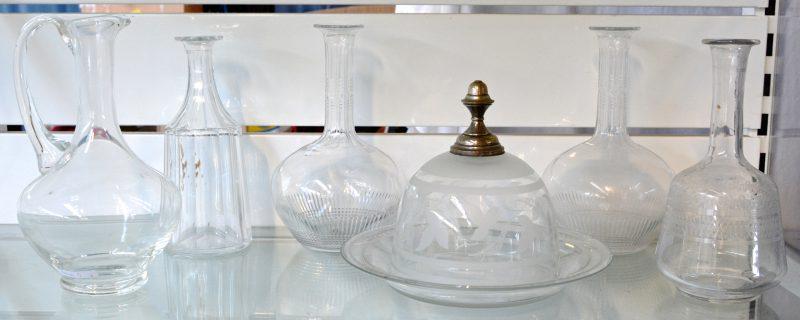 Een lot kleurloos kristal en glaswerk, bestaande uit vier karaffen en een kruik (zonder stoppen) en een stolp met verzilverde dekselknop.
