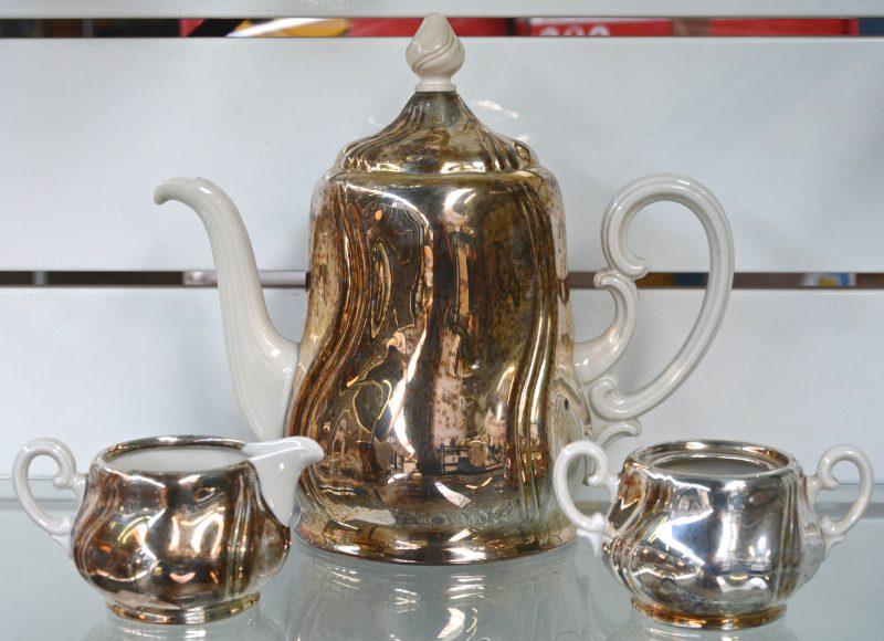 Een driedelig koffiestel van monochroom wit porselein met verzilverde monturen.Onderaan gemerkt. Deksel suikerpot manco.