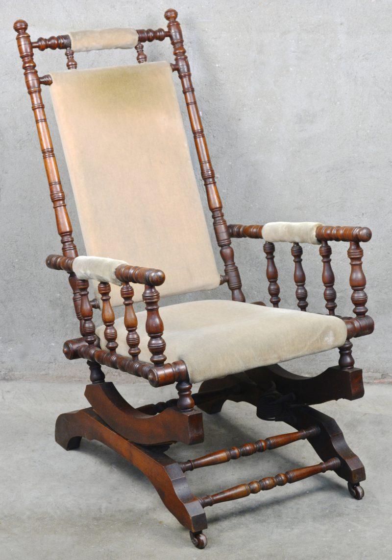 Een antieke schommelstoel van gedraaid mahoniehout en met fluwelen bekleding.