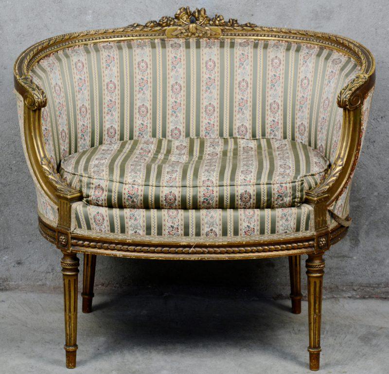 Een kuipfauteuil van gebeeldhouwd en verguld hout in Lodewijk XVI-stijl.