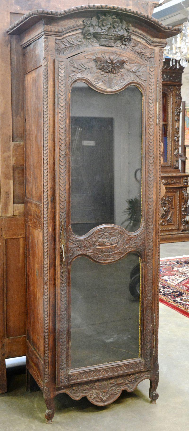 Een eikenhouten ééndeursvitrine met gesculpteerde versieringen. Omstreeks 1800.