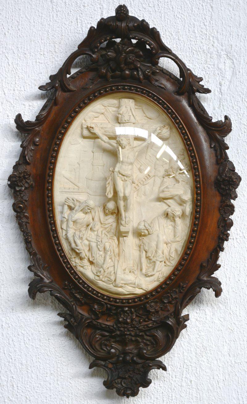 """""""Jezus sterft aan het kruis"""". Een ovaal reliëf van pijpaarde in fraai gebeeldhouwde lijst. XIXe eeuw."""