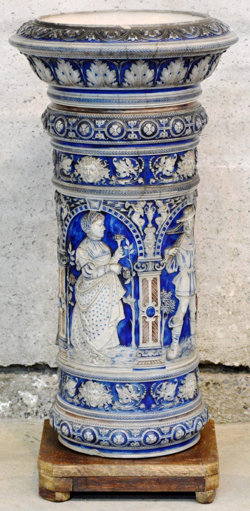 Een plantenstaander van steengoed, versierd met een meerkleurig reliëfdecor.