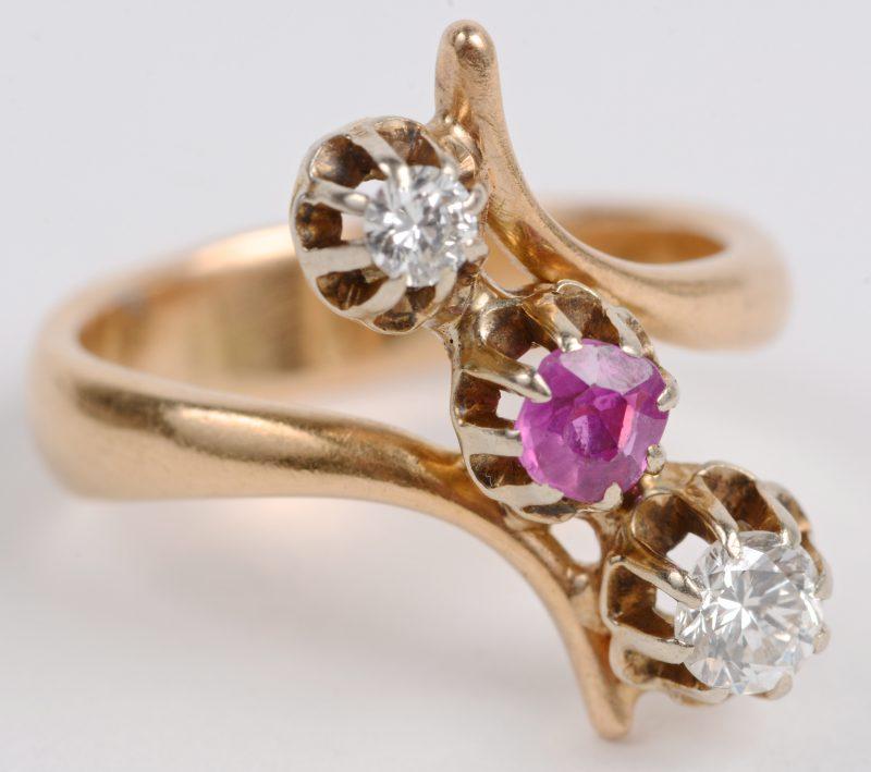 Een 18 karaats geel gouden ring bezet met briljanten met een gezamenlijk gewicht van ± 0,30 ct. en een centrale robijn van ± 0,15 ct.