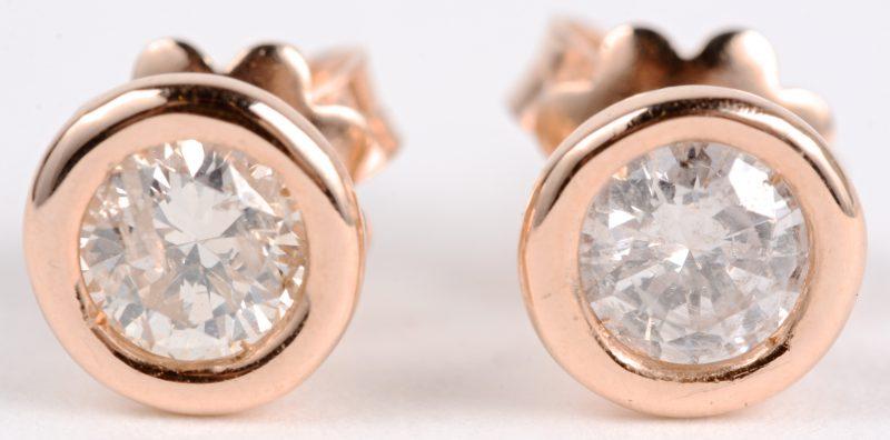 Een paar 18 karaats roze gouden oorbellen bezet met twee briljanten met een gezamenlijk gewicht van ± 0,60 ct.