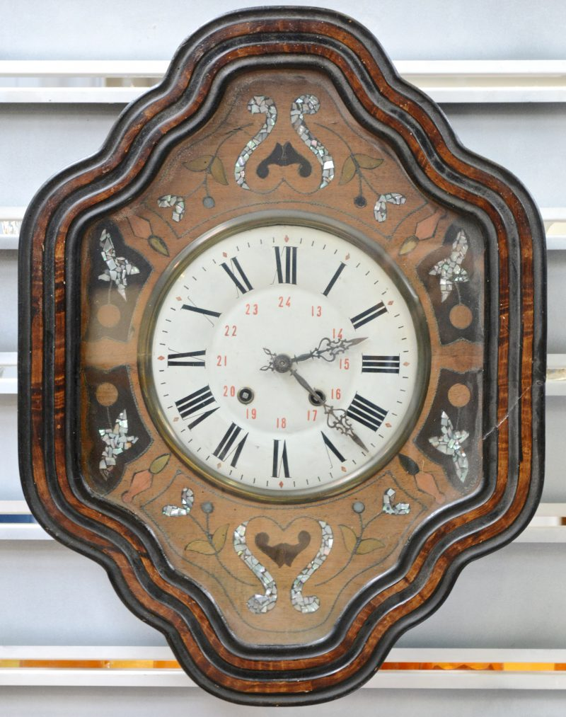 Een oeil-de-boeufklok, versierd met inlegwerk van verschillende houtsoorten en parelmoer.