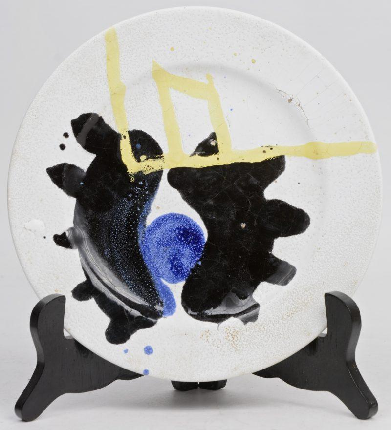 Een handbeschilderd porseleinen bord met surrealistische voorstelling.