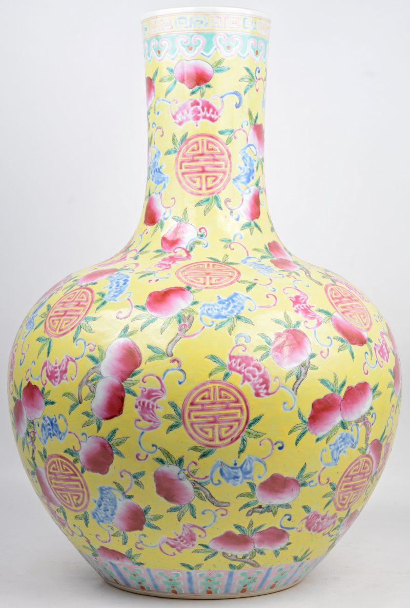 Een grote buikvaas van Chinees porselein, versierd met een meerkleurig perzikendecor op gele fond. Onderaan gemerkt.
