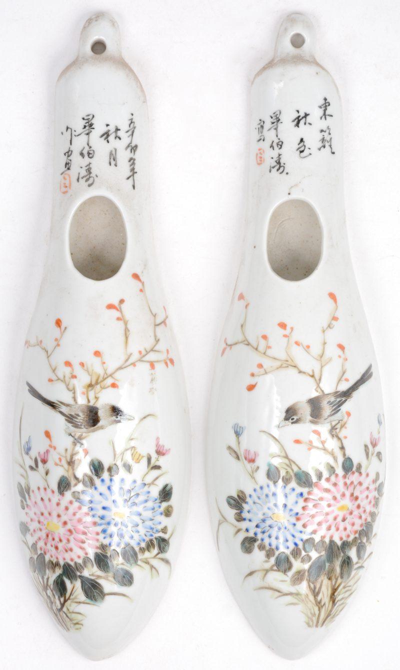 Een paar wandvaasjes van Chinees porselein met een meerkleurig decor van bloemen en vogels.