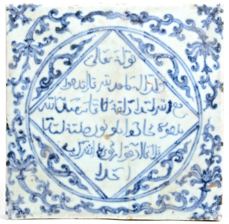 Een porseleinen tegel met Arabische geschriften en motieven in blauw op witte fond.