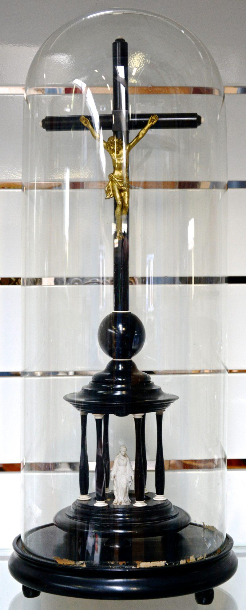 Een gezwart houten kruisbeeld met ivoren versieringen en een messingen corpus. Onder stolp.