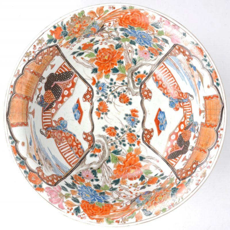 Een grote kom van Arita-porselein, versierd met een decor van figuren, bloeiende takken en vogels. Tijdperk Mei-ji.