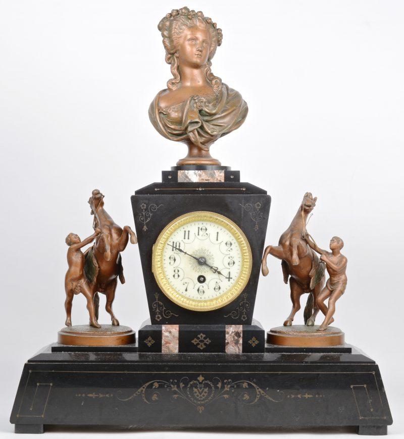 Een schouwpendule van zwart en bruingeaderd marmer, getooid met een zamakken vrouwenbuste en de paardenmenners naar 'Les Chevaux de Marly'. Zonder sleutel. XIXe eeuw.