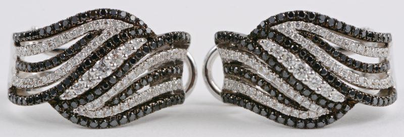 Een paar 18 karaats wit gouden oorbellen bezet met witte en zwarte diamanten met een gezamenlijk gewicht ± 1,28 ct.