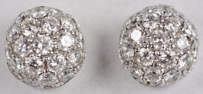 Een paar 18 karaats wit gouden oorbellen bezet met diamanten met een gezamenlijk gewicht ± 0,86 ct.
